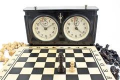 Gammal schackklocka och schackbräde Royaltyfri Foto