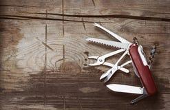 Gammal schweizarekniv på en träbakgrund Arkivbild