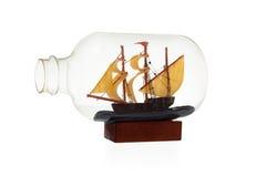 Gammal segelbåt i glasflaskan som isoleras över vit bakgrund royaltyfria bilder