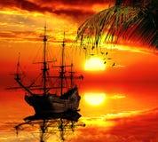 Gammal segelbåt på en solnedgånghorisont royaltyfria foton