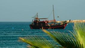 gammal seglingship Sikt till och med blasten av palmträden Arkivfoto