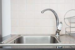 Gammal silvermetallvattenkran i ett kök arkivbilder