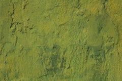 Gammal sjaskig grön gul blå vägg med skrapor, sprickor och fläckar av målarfärg Textur för grov yttersida arkivbild