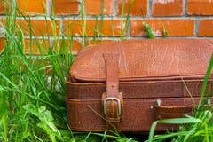 Gammal sjaskig resväska mot bakgrunden av en tegelstenvägg arkivbild