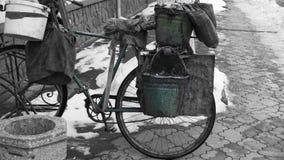 Gammal sjaskig stolpe-apokalyptisk cykel på en svartvit bakgrund arkivfoto