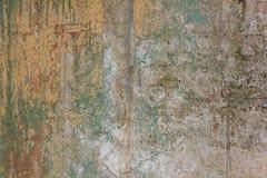 Gammal sjaskig vit gul betongvägg med sprickor, djupa skrapor och fläckar av grön målarfärg och smuts Textur f?r grov yttersida royaltyfria bilder