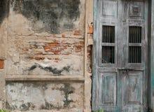 Gammal sjaskiga tegelstenvägg och trägrön dörr Royaltyfri Bild