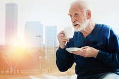 Gammal skäggig man som ser in i avståndet, medan dricka kaffe Arkivfoto
