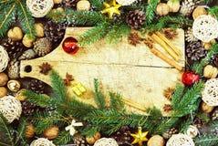 Gammal skärbräda med julattribut på en träkökbakgrund Royaltyfri Fotografi