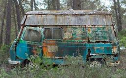 Gammal skåpbil för hippie som överges i skog Royaltyfri Bild