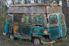 Gammal skåpbil för hippie som överges i skog Royaltyfri Foto