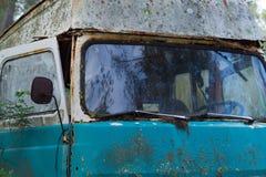 Gammal skåpbil för hippie som överges i skog Arkivfoto