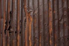 Gammal skadad röd rostig metallvägg Arkivbilder