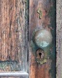 Gammal skalning, wood dörr med den gamla metalldörrknoppen Arkivfoton