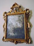 gammal skamfilad guld inramad spegel med utsmyckade barocka detaljer royaltyfria foton