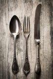 Gammal sked, gaffel och kniv på träbakgrund Royaltyfri Bild