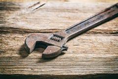 Gammal skiftnyckel på träbakgrund Royaltyfria Bilder