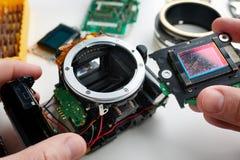 Gammal skrapad digital SLR för bildavkännare kamera i händer av servic Arkivfoton