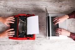 Gammal skrivmaskin och bärbar dator på tabellen Begrepp av teknologiframsteg Arkivfoton