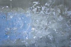 Gammal slagen grå blå betongvägg med skrapor och vita målarfärgfläckar Textur för grov yttersida arkivbilder