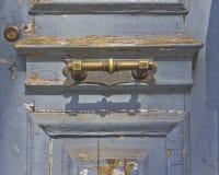 Gammal sliten dörr- och bronshandtagdetalj Arkivfoto
