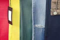 Gammal sliten jeans 6 olika färger, jeansbakgrund, bakgrunden av kläder, sönderriven jeans och tom etikett arkivfoto