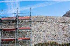 Gammal slottvägg med materialet till byggnadsställning Arkivbilder