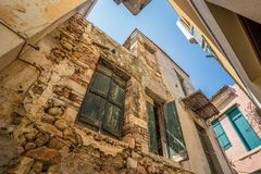 Gammal smal gata med stenväggar och träfönster i den Chania staden, Grekland Arkivfoton