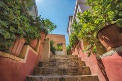 Gammal smal gata med stenväggar och träfönster i den Chania staden, Grekland Arkivbild