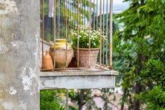 gammal smula balkong med blomkrukor royaltyfria foton