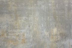 Gammal smutsig betongv?gg med vita och gula fl?ckar av m?larf?rg och skrapor Textur f?r grov yttersida royaltyfri foto