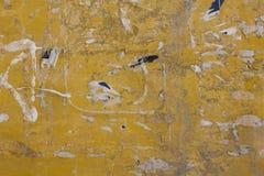 Gammal smutsig gul betongv?gg med skada, skrapor, gr?a m?larf?rgfl?ckar och kvarlevor av s?nderrivna pappers- annonser Textur f?r fotografering för bildbyråer