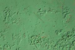 Gammal smutsig skadad grön betongvägg med skrapor och svarta hål Textur för grov yttersida royaltyfri foto