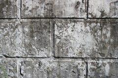Gammal smutsig vägg med rektangulära tjock skiva och rest av ett bortförklaringlager Royaltyfria Foton
