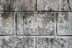 Gammal smutsig vägg med rektangulära tjock skiva och rest av ett bortförklaringlager Arkivfoto