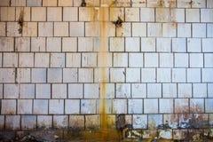 Gammal smutsig vägg med tegelplattor för vit fyrkant arkivbilder