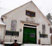 Gammal smutsig vit New England ladugård med gröna dörrar och mång--panel dörrar Royaltyfri Fotografi