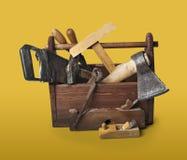 Gammal snickareWooden toolbox med hjälpmedel som isoleras på vit arkivbild