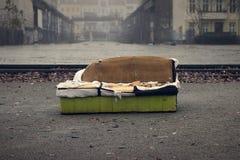 Gammal soffa i en smutsig stad arkivbilder