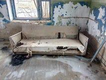 Gammal soffa, tomt hus, brist av folk, brutet fönster, i dålig kondition möblemang, tomhet, icke-bostads- lokal, sjaskiga väggar, Royaltyfria Foton