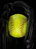 Gammal softball i en handske Arkivbilder