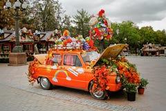Gammal sovjetisk bil Zaporozhets som dekoreras med gulingsidor, blommor och saker på ` för höst för festival`-Moskva i Novopushki Arkivfoton