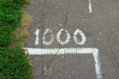 Gammal sprucken motionsslinga markera 1000 på asfalt royaltyfria foton
