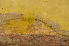 Gammal sprucken vägg med gul och röd brun murbruk Royaltyfria Bilder
