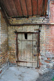 Gammal stängd dörr i gammalt övergivet hus Arkivbild