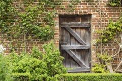 Gammal stängd trädörr i en tegelstenvägg i en trädgård Royaltyfri Bild
