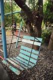 Gammal stålgunga på fältet av stads- parkerar Arkivfoto