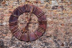 Gammal stålklocka på slottväggen Royaltyfri Bild