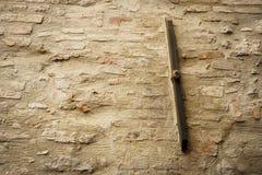 Gammal stång för ankare för metallstång på en tegelsten- och stenmurverkvägg Arkivfoto