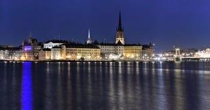 Gammal stad i Stockholm med ön Riddarholmen framtill på natten Arkivfoton